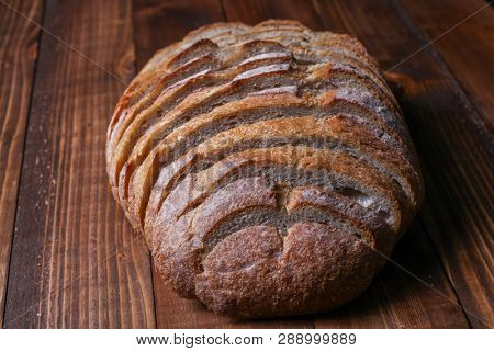 Whole sliced bread on wooden background