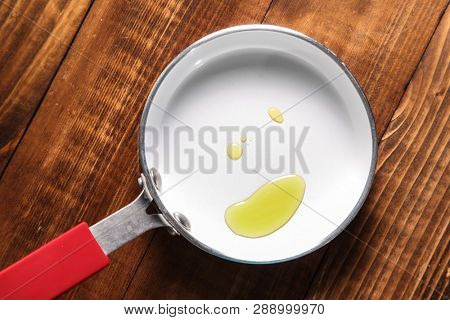 Fry pan with oil on wooden background close up
