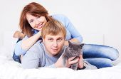 happy young couple on the bed at home with their cat (focus on the  man) poster