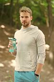 Athlete hold plastic bottle on fresh air. Thirst. Macho relax with water bottle after workout in park. Relax in forest. Stay hydrated and healthy. Water is part of healthy training. Sport and fitness. poster
