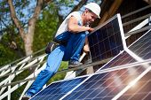 Professional technician adjusting heavy solar photo voltaic panel to high metal platform on blue sky and green tree background. Stand-alone solar system installation, green energy production concept. poster