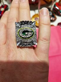 Person Wearing A Green Bay Packers 2010 Super Bowl Ring Replica On His Right Hand Ring Finger, Chica