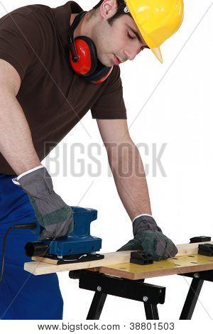 carpenter at work with sander machine