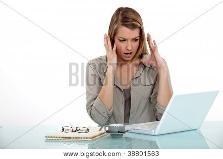 angry businesswoman looking at her laptop