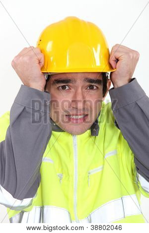 Construction worker protecting his head