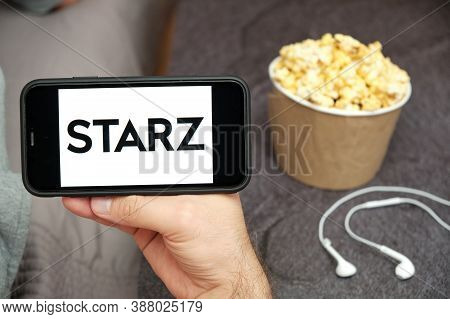 Starz Logo On The Mobile Phone Screen With Popcorn Box And Apple Earpods On The Background, Septembe