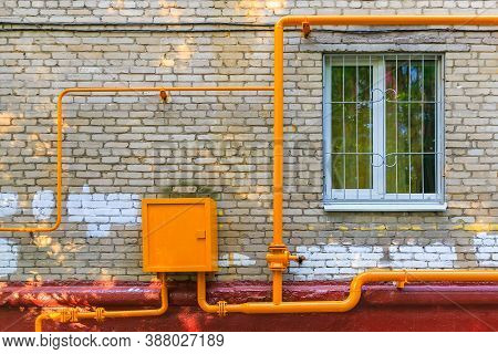 Orange Pipes Of Gas Hub With Tap For Supplying Household Gas To Residential Building On The Wall Of