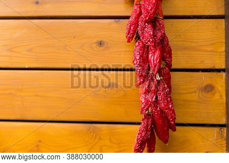 Red Chili Peppers On The Background Of The Old Wooden Wall.string Of Fresh Organic Peppers Is Hangin