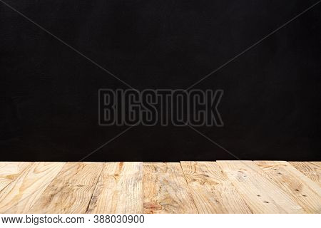 Empty Wooden Deck Table Over Black Wall Background. Mock Up Template. Copy Space