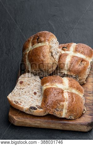 Easter  Wholemeal Hot Cross Buns On Wooden Board On Black Stone Background