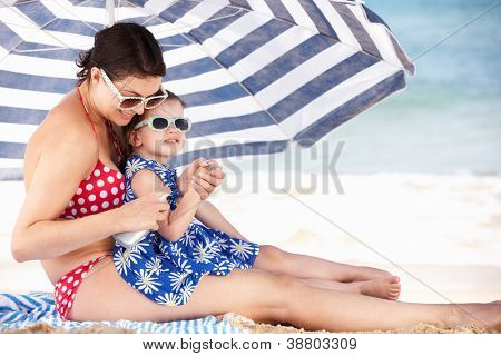 Mother And Daughter Under Beach Umbrella Putting On Sun Cream