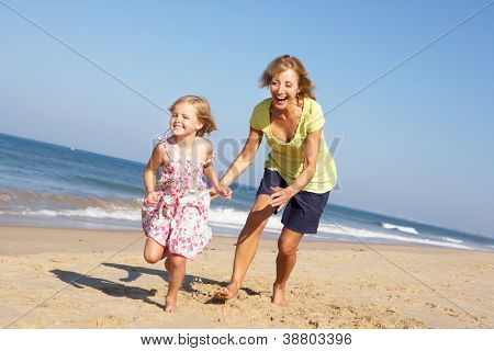 Grandmother And Granddaughter Running Along Beach