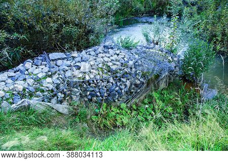 Reinforcement With Stones Of The Gully Zone By The Stream During Afternoon Outdoors In Summer.