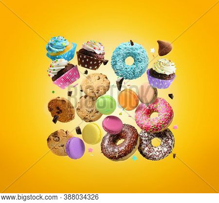 Cakes, Sweets, Confectionery Background. Donuts, Cookies Cupcakes Macaroons Flying Over Yellow Backg