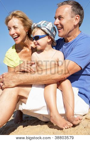 Grandparents And Grandson Sitting On Beach