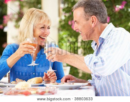 Senior Couple Enjoying Meal outdoorss poster
