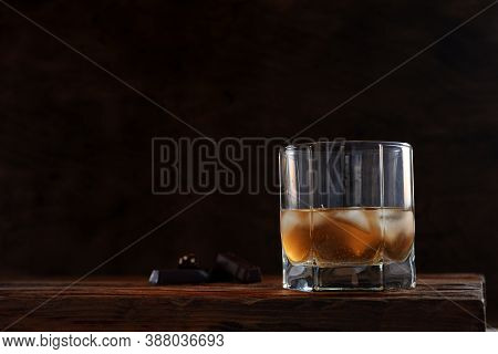 Whiskey With Ice Cubes. Cold Alcoholic Drink In A Glass Stock On Wooden Table Over Dark Background W