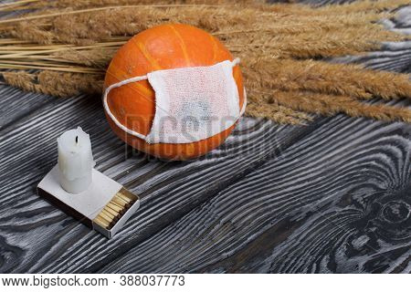 Orange Pumpkin In A Medical Mask. Lies On Black Pine Boards. Nearby There Is A Candle Stub And A Bou