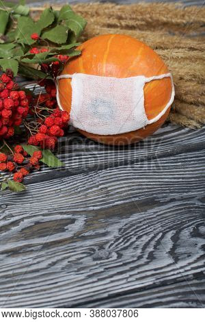 Orange Pumpkin In A Medical Mask. Lies On Black Pine Boards. Nearby Is A Bouquet Of Dried Grass And