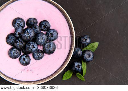 Tasty Fresh Blueberry Yoghurt Shake Dessert In Ceramic Bowl Standing On Black Table Background. Home