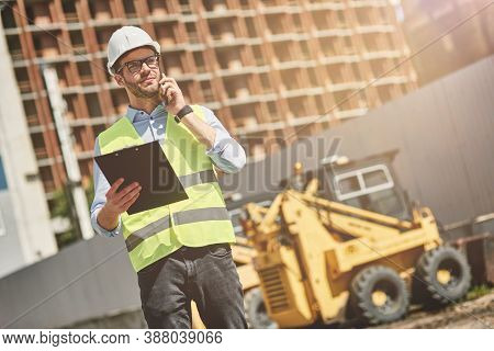 Important Call. Young Civil Engineer Or Construction Supervisor Wearing Helmet Talking By Phone Whil