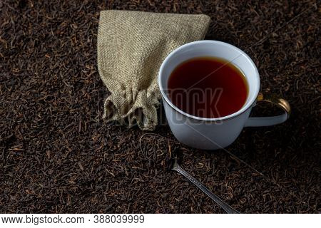 Leaf Tea. A Lot Of Loose Tea. A Cup Of Tea Stands On Loose Tea