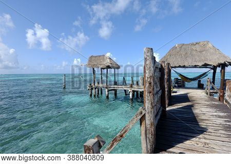Rustic Wooden Pier On The Sea. Unrecognizable Young Tourist Rests On A Hammock At The End Of A Woode