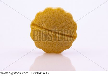 Single Beige Pill Isolated On White Reflective Surface. Global Pharmaceutical Industry For Billions