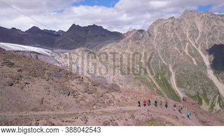 Aerial View Of Hiking Team Walking One By One, Climbing Up The Mountain Slope. Clip. Travel And Spor