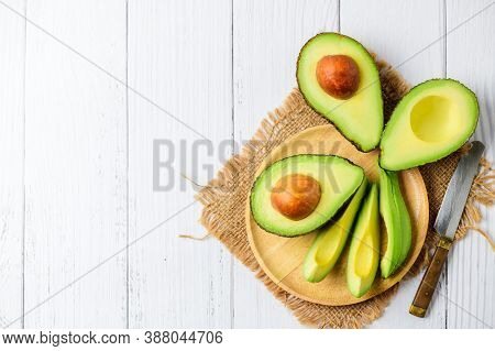 Top View Of Avocado On Wood Plate And White Wood Background With Copy Space. Ripe Fresh Green Avocad