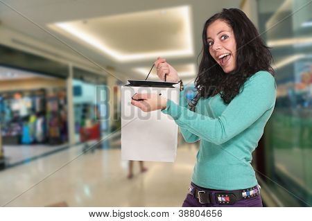 Happy brunette showing her purchases in a mall