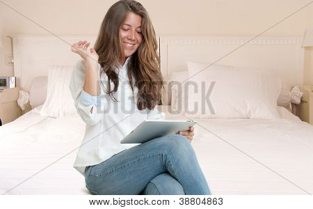 Young woman sitting on a bed using a digital tablet