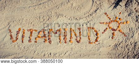 Inscription Vitamin D With Shape Of Sun Made Of Amber Stones On Sand At Beach. Prevention Of Vitamin