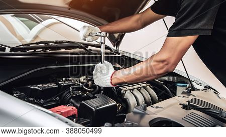 Close-up Hands Of Auto Mechanic Are Using The Wrench To Repair A Car Engine In Auto Car Garage. Conc