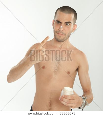 Man with funny face applying face cream
