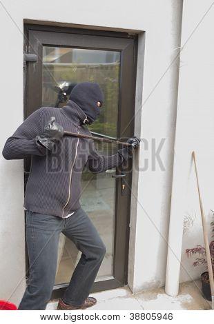 Burglar breaking door from outside with crow bar
