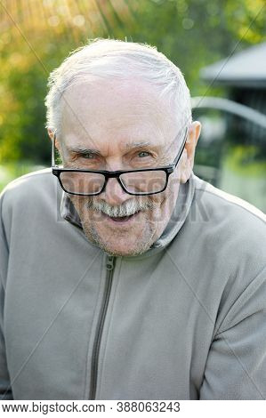 Cheerful Gray-haired Old Man Looks At The Interlocutor And Smiles. The Old Man Cant See Very Well Wi