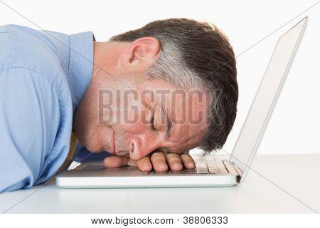 Businessman sleeping on his laptop on his desk