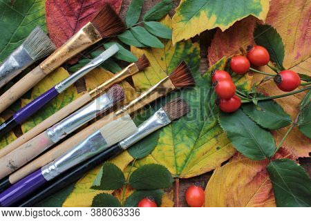 Autumn Creative Flat Lay Composition With Brushes For Painting, Fall Leaves, And Red Berries. Fall C