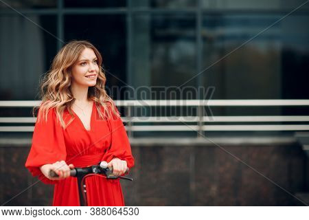 Young Woman With Electric Scooter In Red Dress At The City
