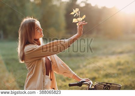 Happy Active Young Woman Holds Fall Leaves In Hand And Ride Bicycle In Autumn Park