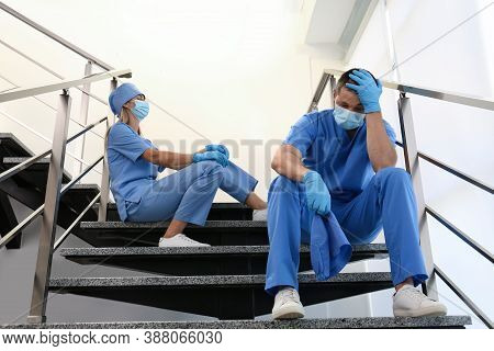 Exhausted Doctors Sitting On Stairs Indoors. Stress Of Health Care Workers During Covid-19 Pandemic