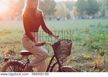 Happy Active Young Woman Riding Vintage Bicycle With Basket In Autumn Park At Sunset