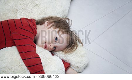 Unhappy Child Boy Lies On The Floor At Home Or In Kindergarten Among Toys And Is Sad Or Falls Asleep