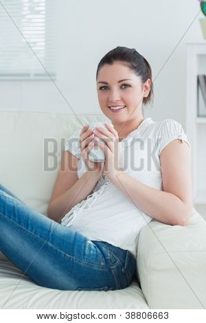 Smiling woman sitting on the couch in the living room and holding a mug