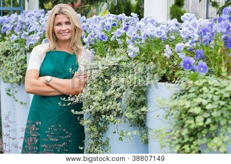 Employee leaning against wall with purple flowers in garen center