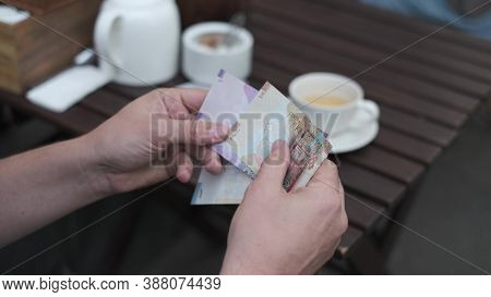 Man Counts Kuwaiti Dinars Banknotes To Pay For Coffee In A Street Cafe