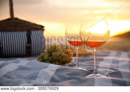 Blanket With Glasses Of Wine And Food On Beach At Sunset. Romantic Picnic For Couple