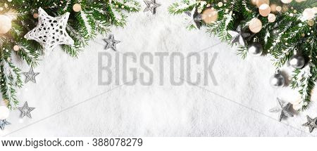 Christmas Background, Green Pine Branches, Cones On Snow Background And Light. Creative Composition