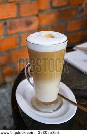 Latte Coffee Macchiato In Tall Glasses With Table Settings In Street Cafe. Red Brick Wall Background